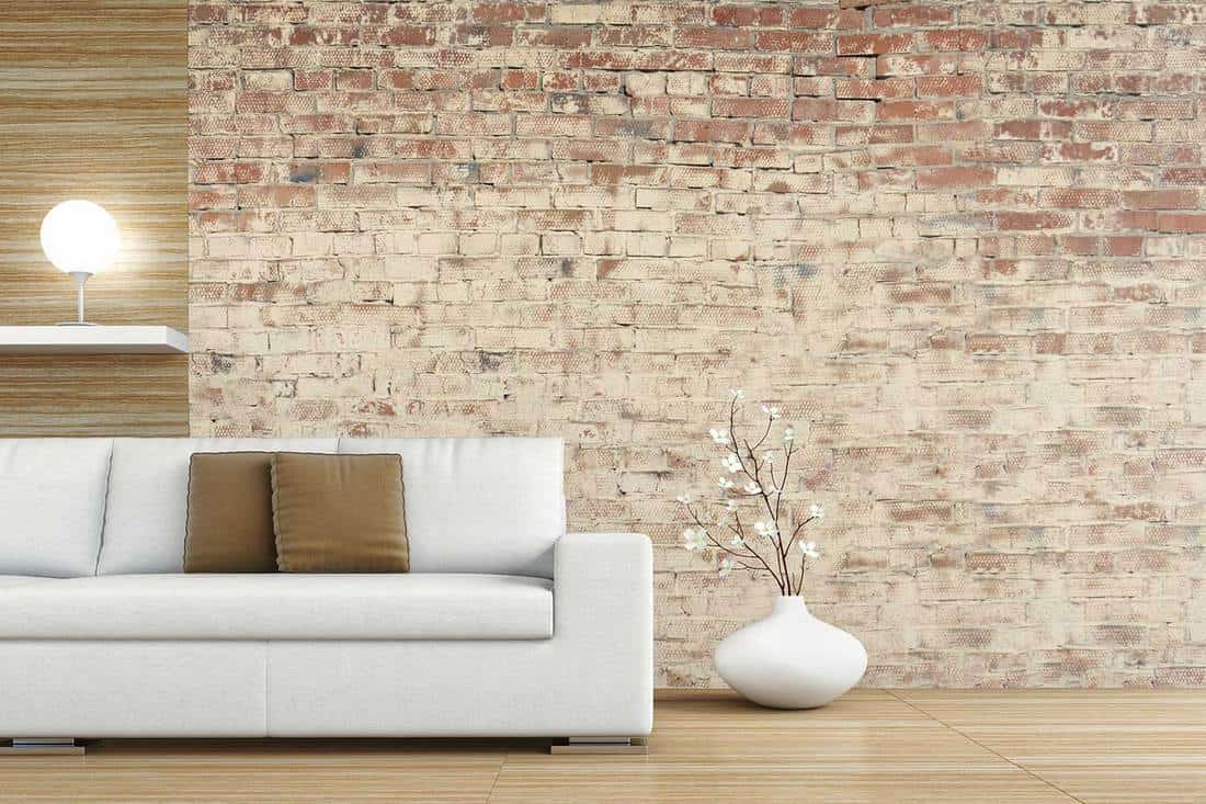 Living room with white sofa and decoration on hardwood floor in front of brick ruined wall
