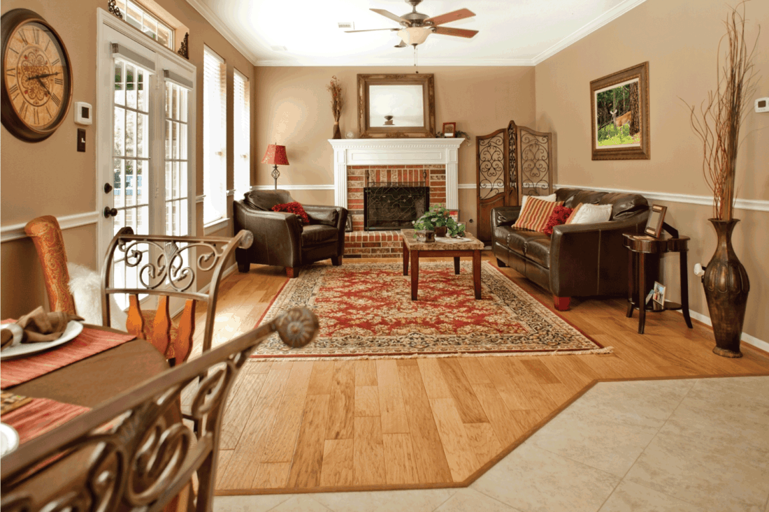 Lovely living room area of showcase home. Decor is red and tan color scheme. Seating area, fireplace. Breakfast table in foreground. Hardwood, tile floors.