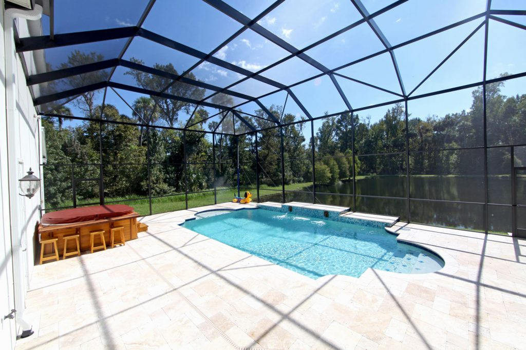 Luxurious interior of a screen pool housing with a small pool on the middle next to a large lake