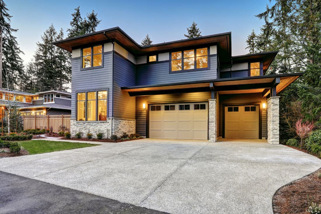 Luxurious new construction home in Bellevue, WA. Modern style home boasts two car garage framed by blue siding and natural stone wall trim