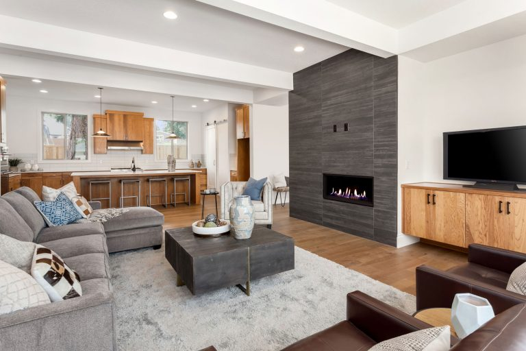Luxurious open space living room and kitchen area with wooden tile flooring, area rug under the furnitures, and modern furnitures complementing the overall architecture, How To Install Recessed Lighting In The Basement