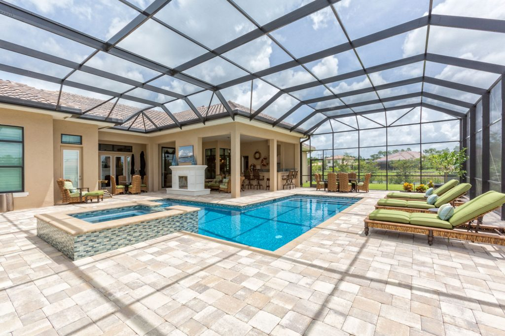 Luxurious screen lanai design with beautiful tile flooring and a small pool with a jacuzzi on the side