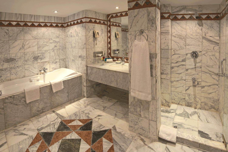 Luxury hotel bathroom suite with large bathtub, vanity, and shower. recessed lighting