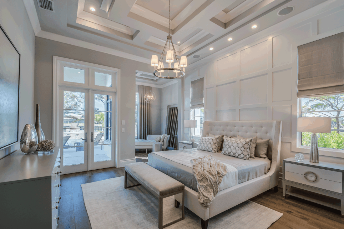 Master bedroom with high coffered ceiling and wainscoting wall
