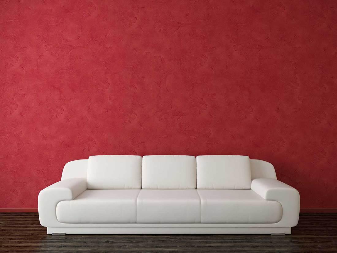 Modern white sofa near red venetian stucco wall