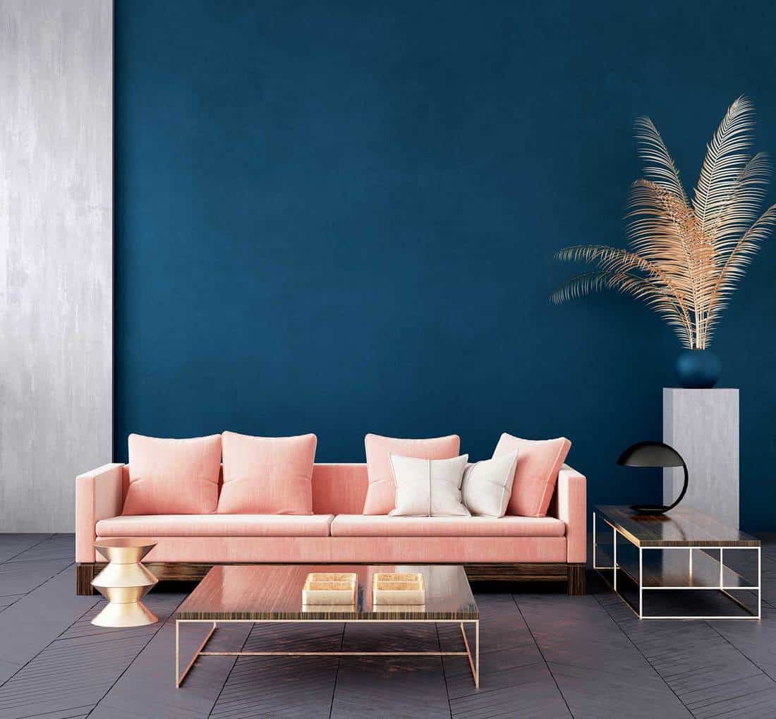Modern dark blue living room interior with pink color couch and golden decor