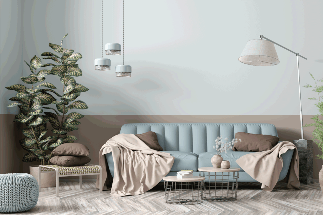 Modern interior of apartment, living room with blue sofa, floor lamp, coffee tables and plant