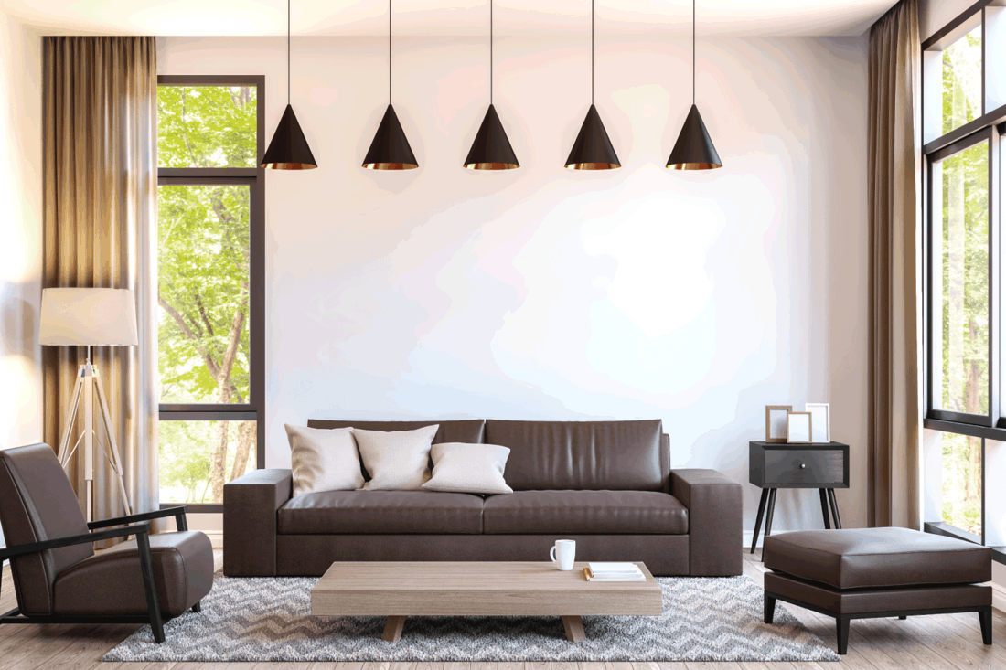 Modern living room decorate with brown leather furniture image.There are large window overlooking to nature and forest