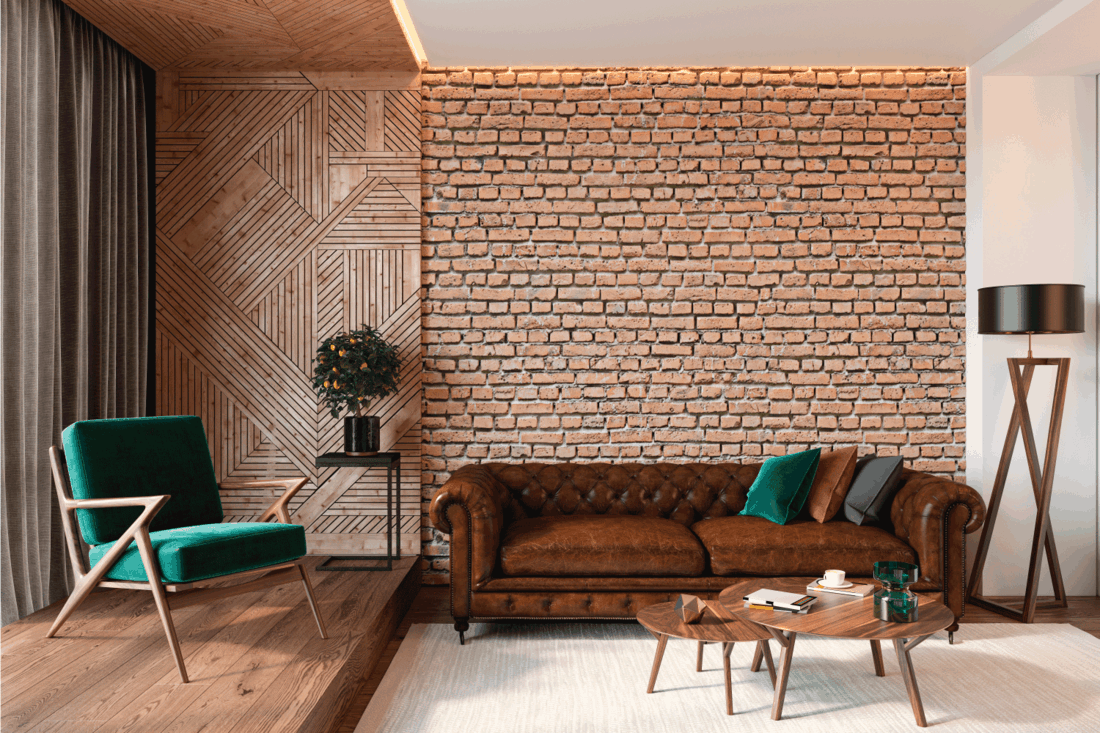Modern living room interior with brick wall blank wall, leather brown sofa, green lounge chair, table, wooden wall and floor, plants, carpet, hidden lighting