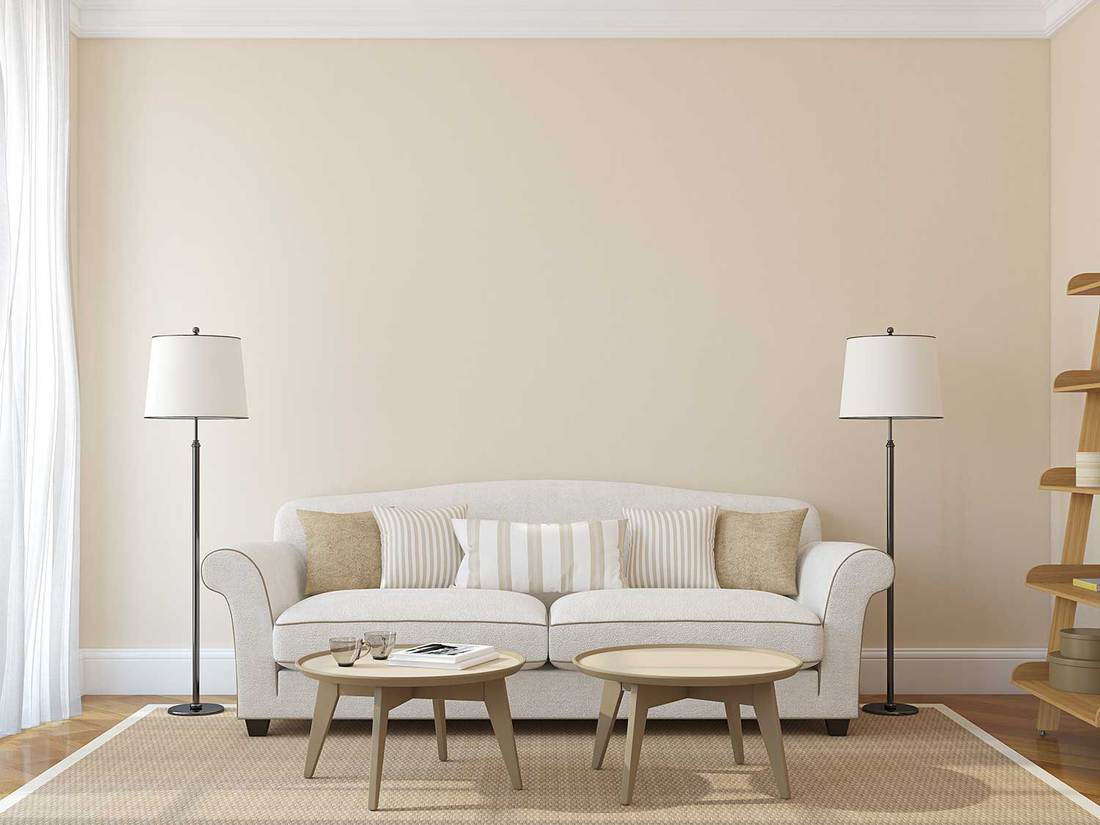 Modern living room with white sofa, standing lamps and wooden coffee tables