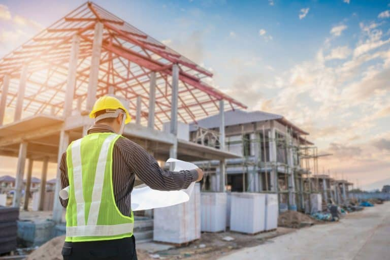 Professional engineer architect worker with protective helmet and blueprints paper at house building construction site, How Long Does A New House Take To Build - By Type Of House