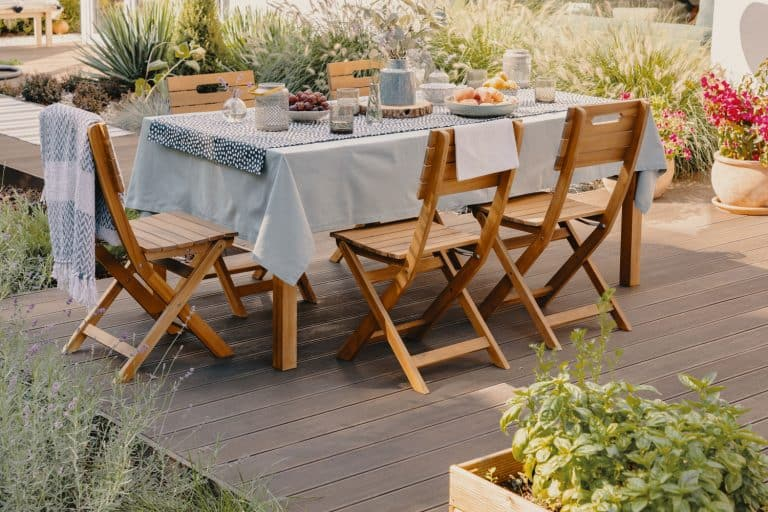 Rustic themed outdoor dining area with wooden chairs, white tablecloth, and incorporated with plants and herbs, How Far Should A Tablecloth Hang? [Should It Touch The Floor?]