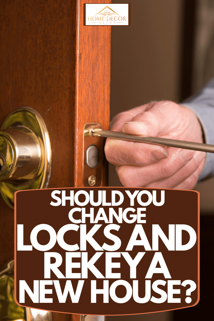 A man installing a new lock to the hardwood front door, Should You Change Locks And Rekey A New House?