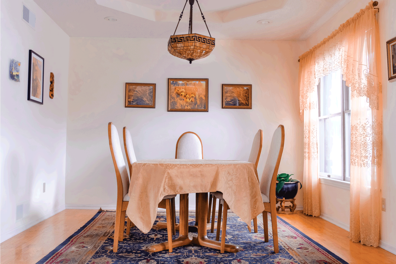 Straight view of dining room with table covered with tablecloth and four teak and fabric chairs and large with with curtains; oriental rug under table