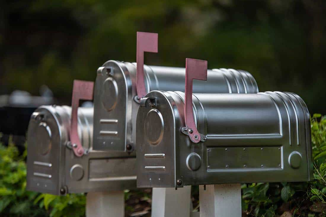 Three silver metallic mailboxes with pink flags on green blurred background