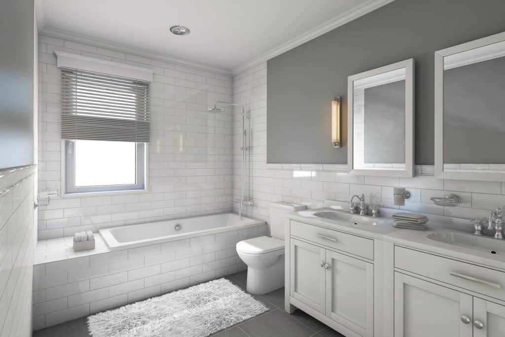 White and gray color themed bathroom with a gray wall vanity, white tiled bathtub backsplash, and white cabinetry