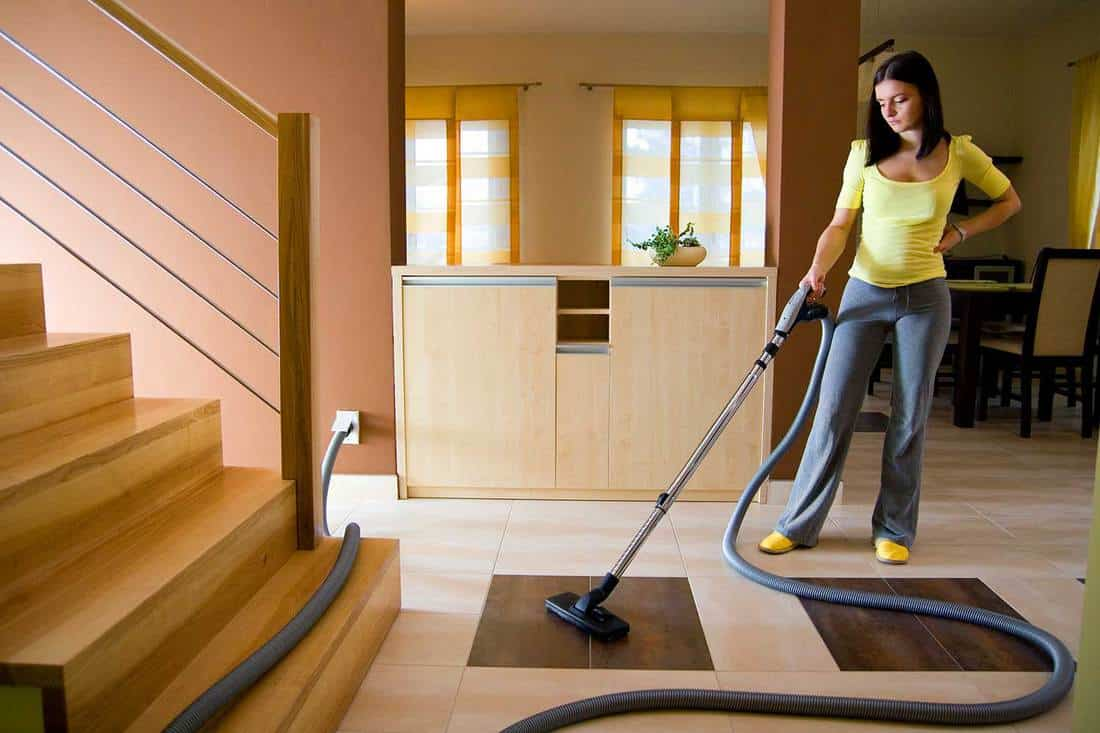 Young woman cleaning floor using a central vacuum system