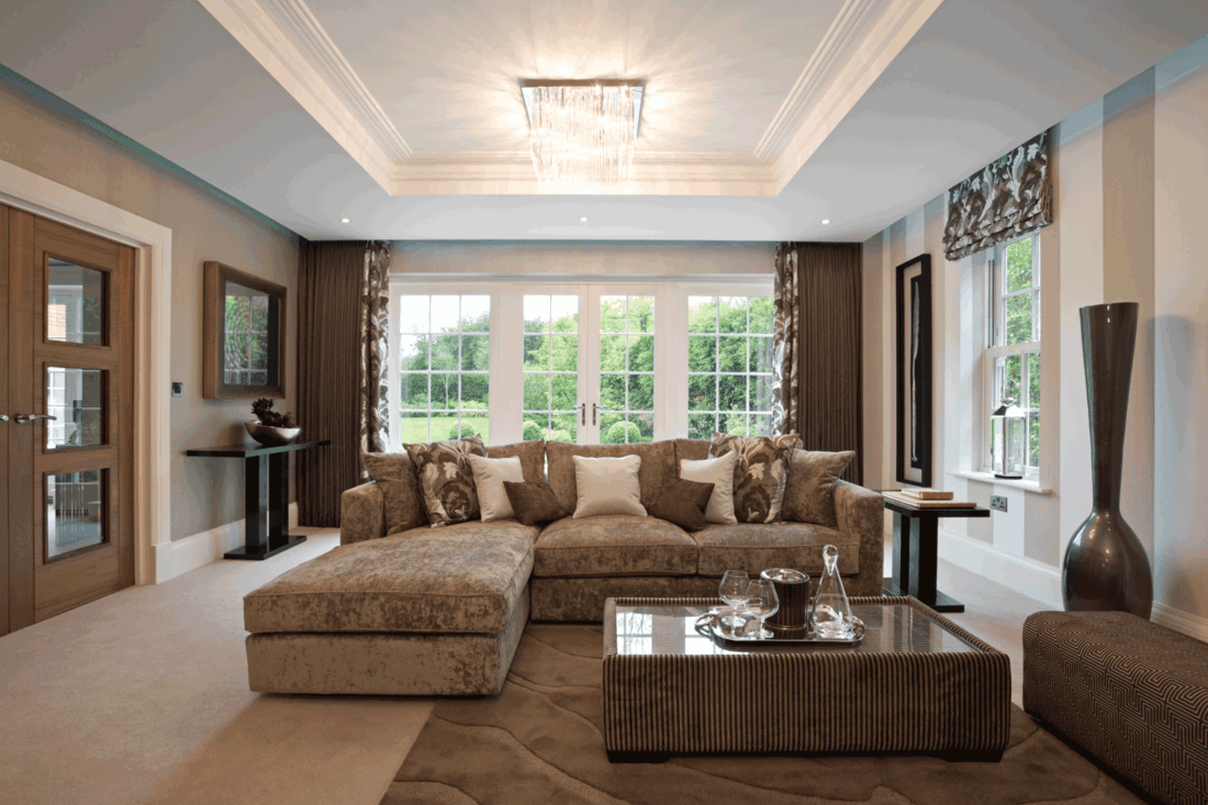 gorgeous lounge in a luxury new home dressed in shades of brown, beige and bronze. A suspended-glass lighting unit sits in a large recess with cornices