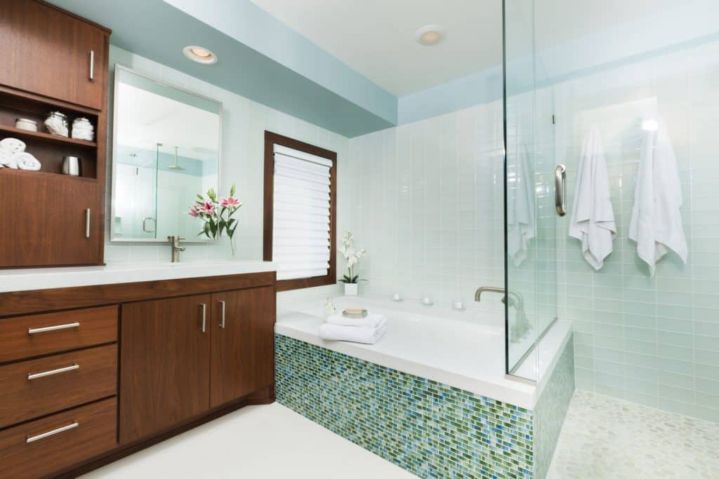 Interior of a white modern bathroom with a glass wall on the bathtub and a wooden cabinetry