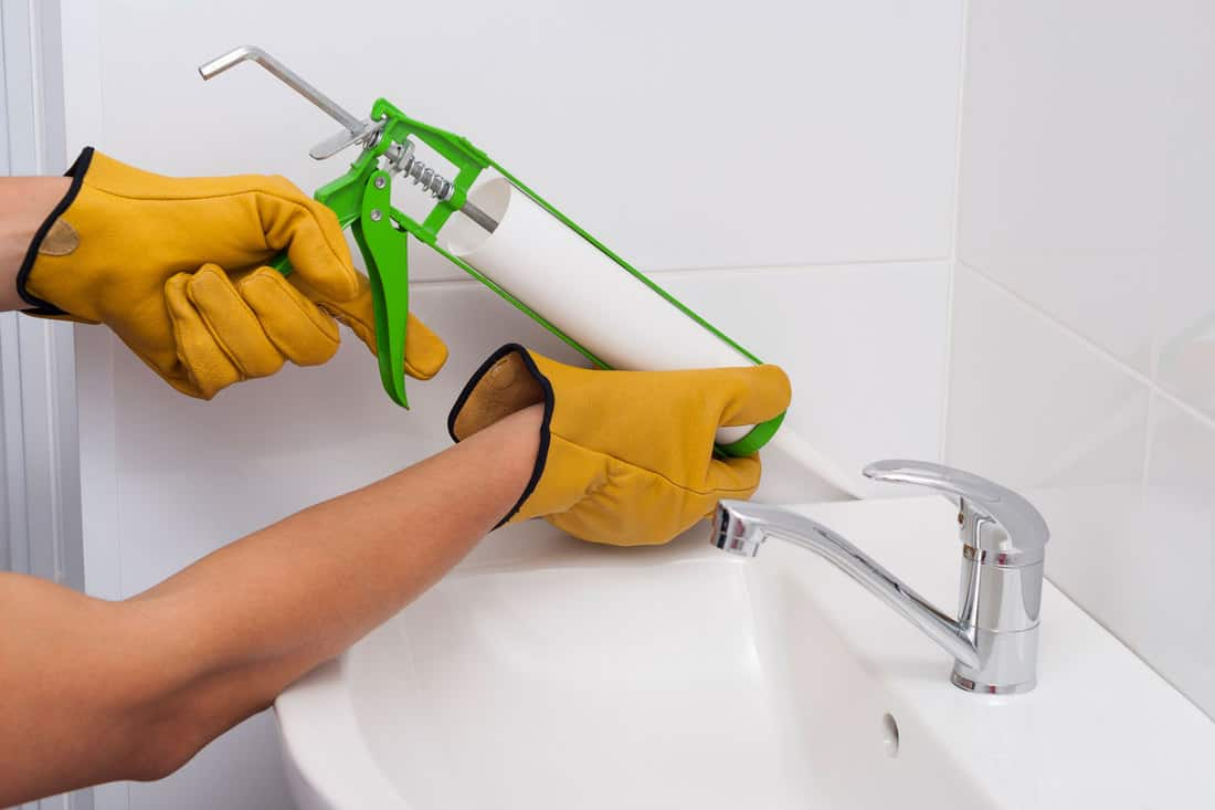 plumber fills the seam between the sink and the tile with a silicone sealant, 7 Types Of Caulk For The Bathroom [And Which To Choose]