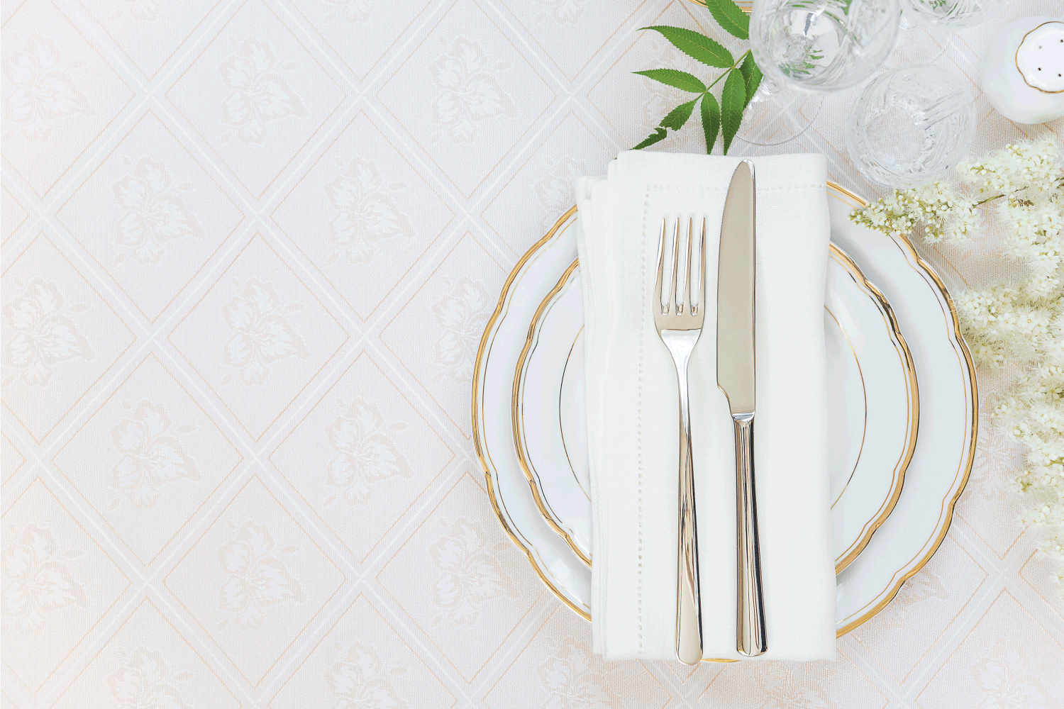 silver cutlery on top of table napkin on a set of ceramic flatware on a table with tablecloth