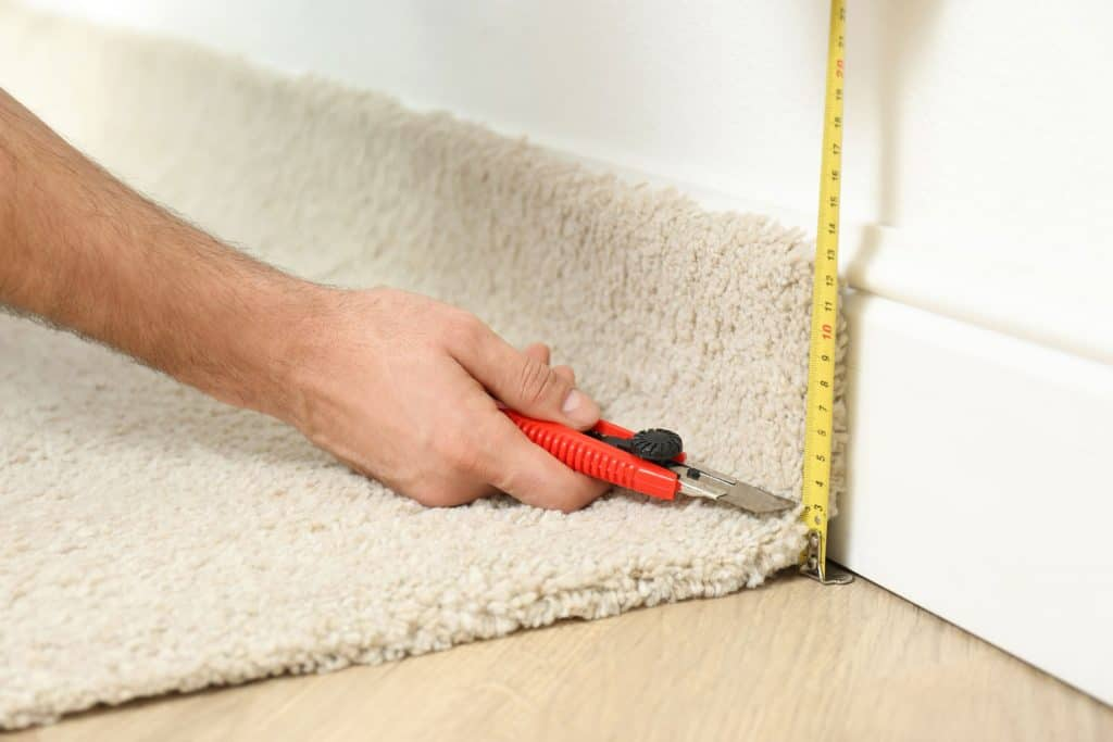 A carpet installer measuring the carpet and using a cutter to trim it