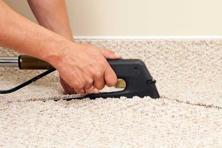 A carpet installer using a seam iron to join two sections of berber carpet in a bedroom, How Hot Does A Carpet Iron Get?