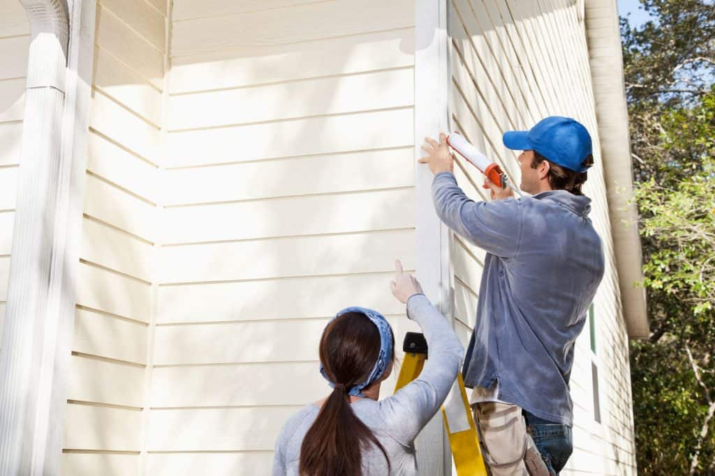 A couple caulking the wooden siding of their house