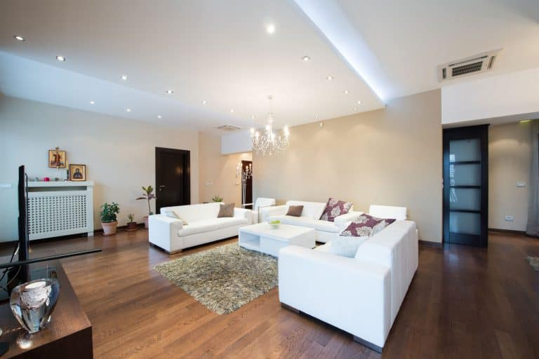 A gorgeous basement with laminated flooring, white painted walls, and pot lighting, Carpet Vs Laminate In A Basement - What To Consider