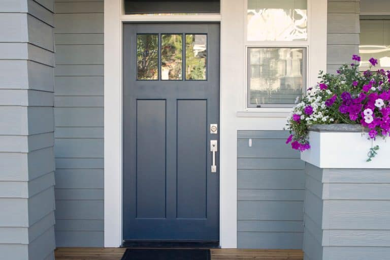A gray front door of a home with front porch and flowers, What Color Door Knobs With Grey Doors?