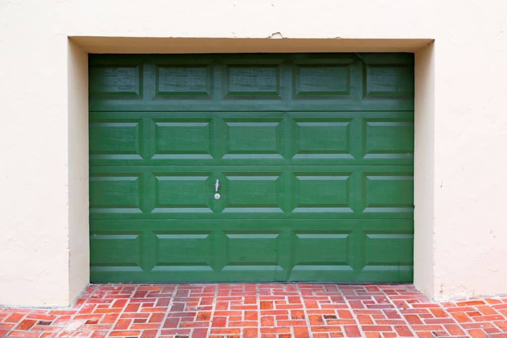 A green colored garage door with white painted walls