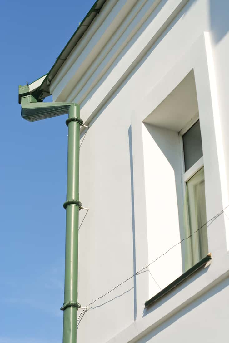 A green gutter system on a white house