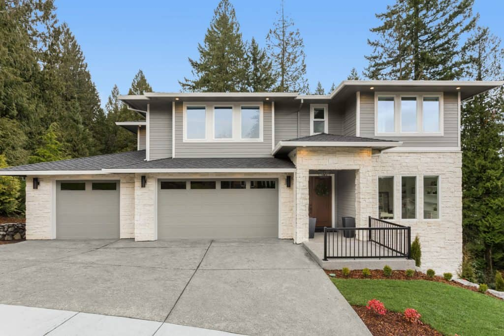 A huge gray colored wooden siding mansion with two huge gray garage doors