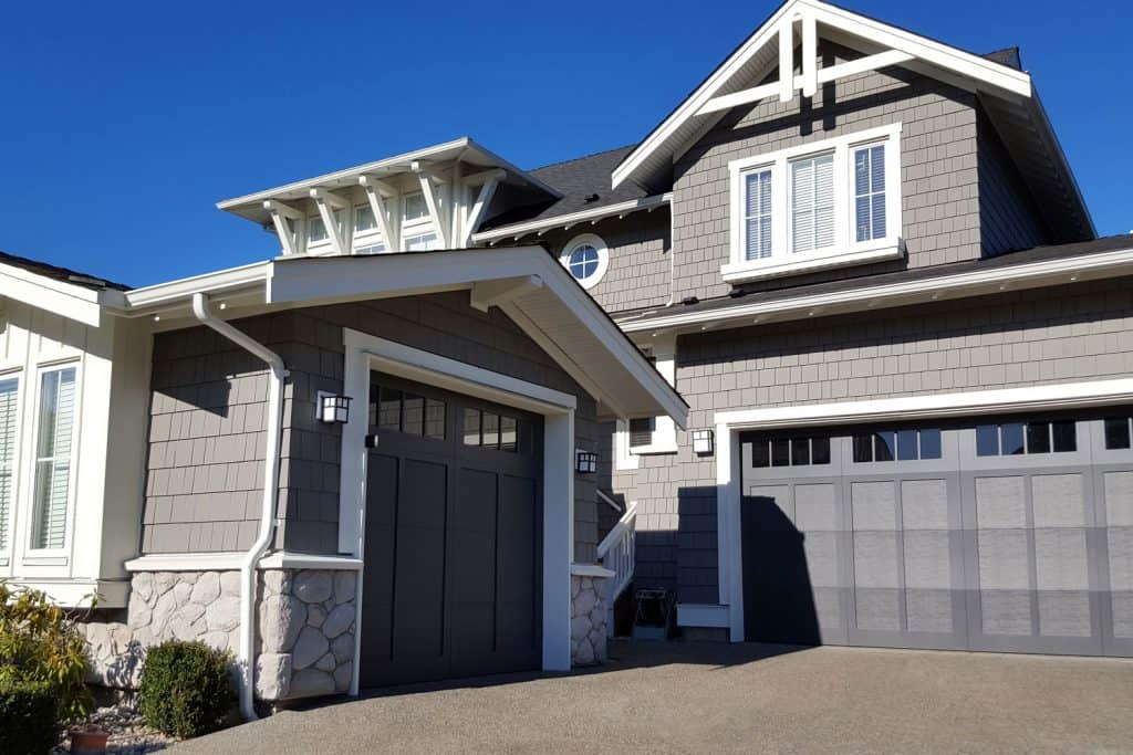 A huge two storey mansion with gray shingle roofing and sidings and a gray garage door with white painted window frame