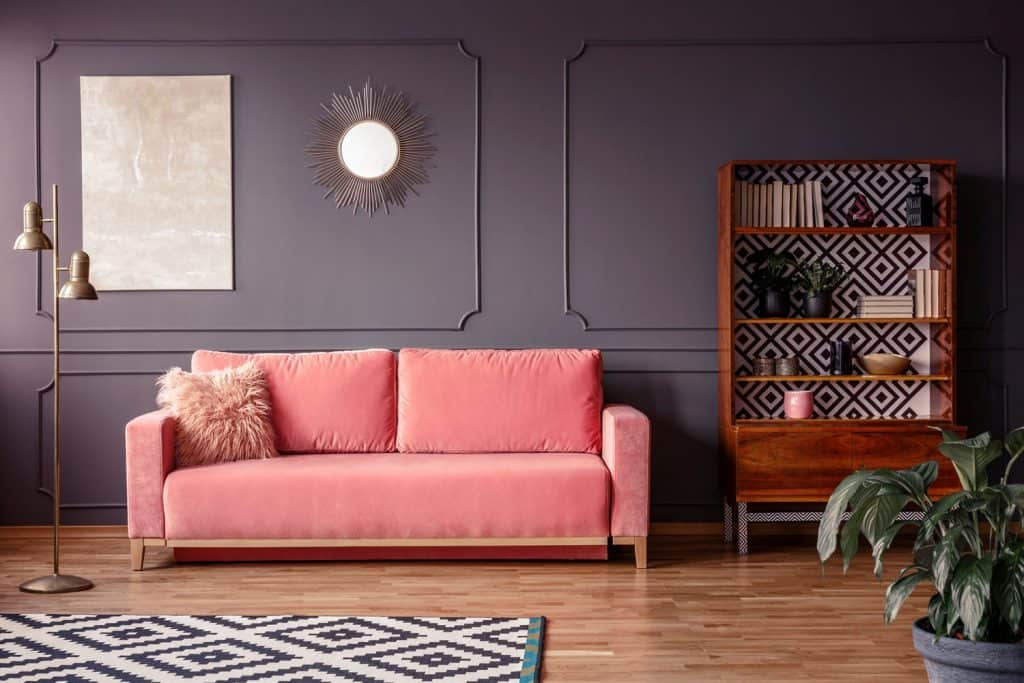 A light purple flat paneled wall with wooden laminated flooring and a pink colored sofa with a suede throw pillow