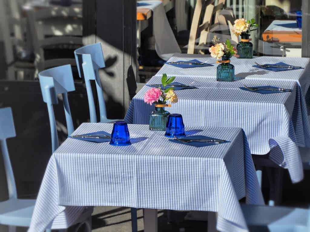 A line of cute square tables with patterned blue and white tablecloths and flowers on them