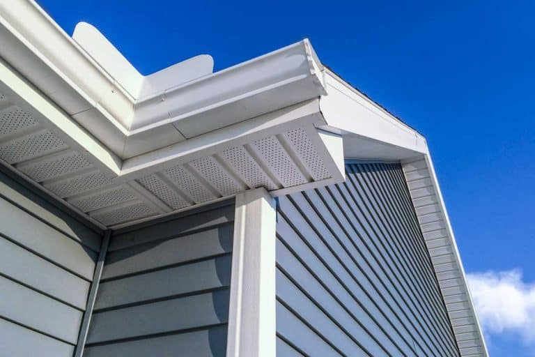 A low angle view of soffit, gutters, downspout and vinyl siding on a new home, What Color Gutters To Choose [By House Color]