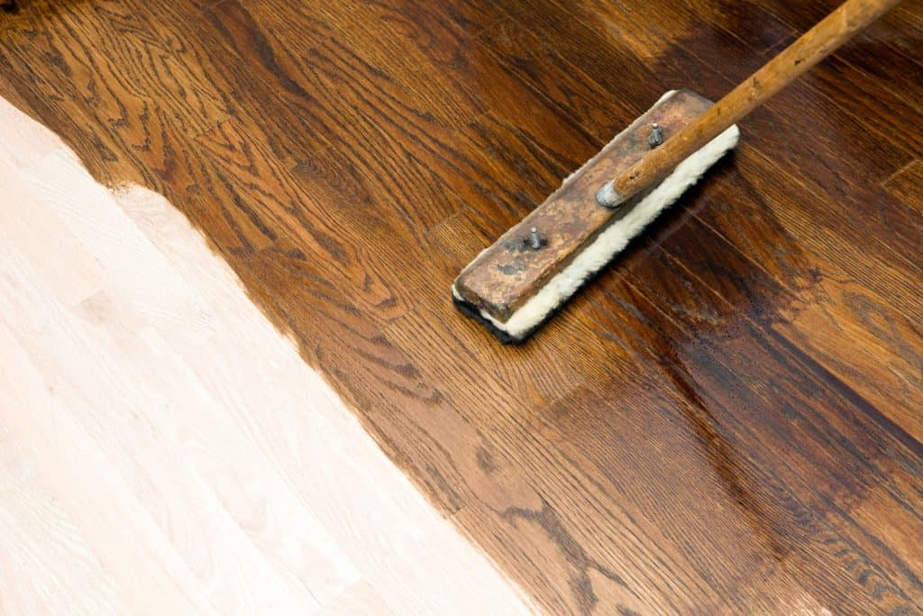 A man applying a new color on the sanded flooring