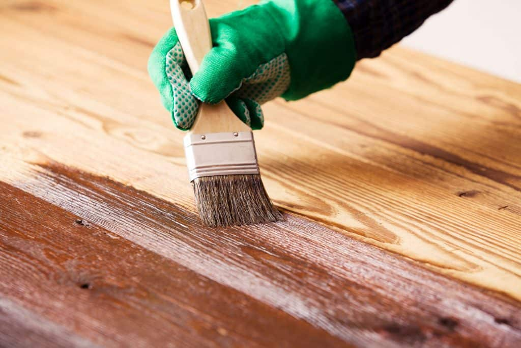 A man applying a new color on the wooden flooring