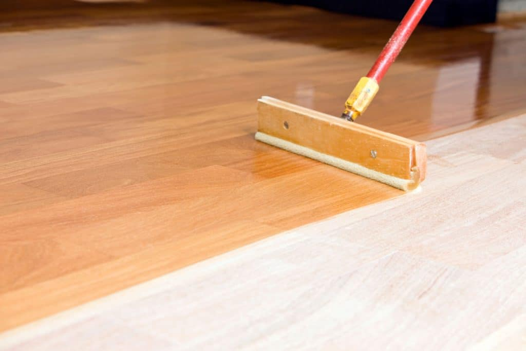 A man applying a new pattern on sanded flooring