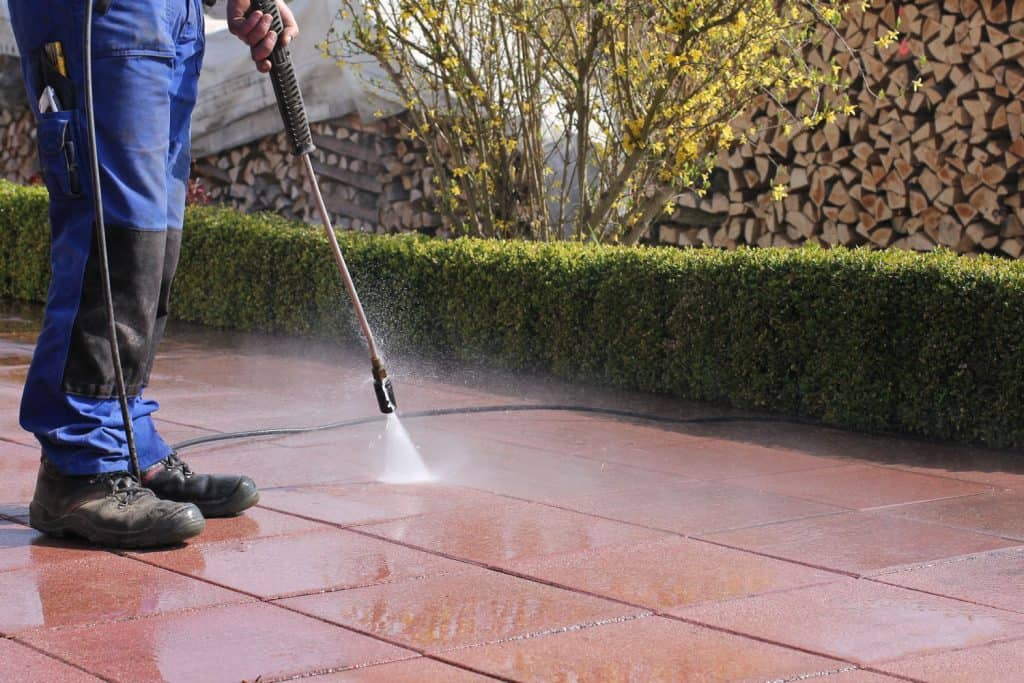 A man cleaning the brown tiles using a power sprayer