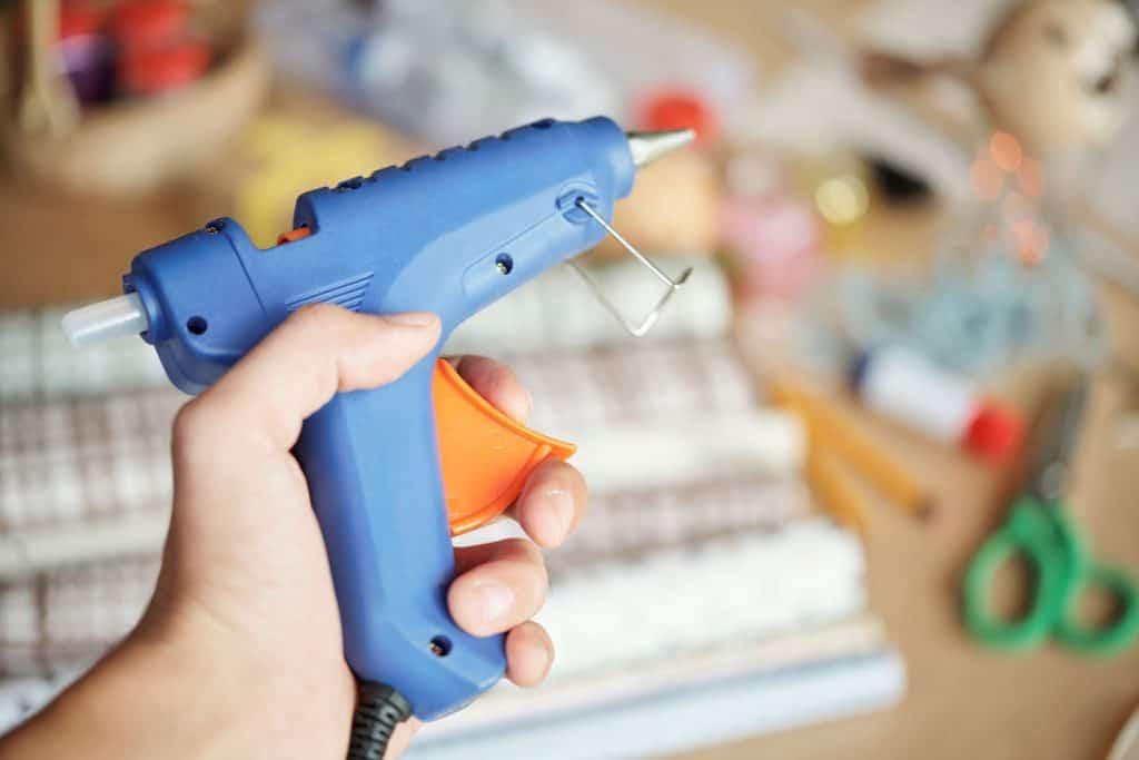 A man holding a small glue gun