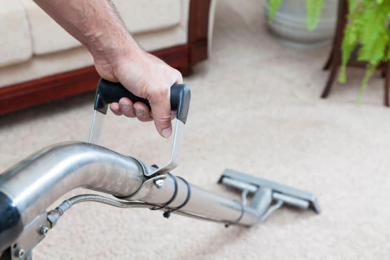 A man steam cleaning the carpet inside his living room, How To Remove Sticky Residue From Carpet Protection Film