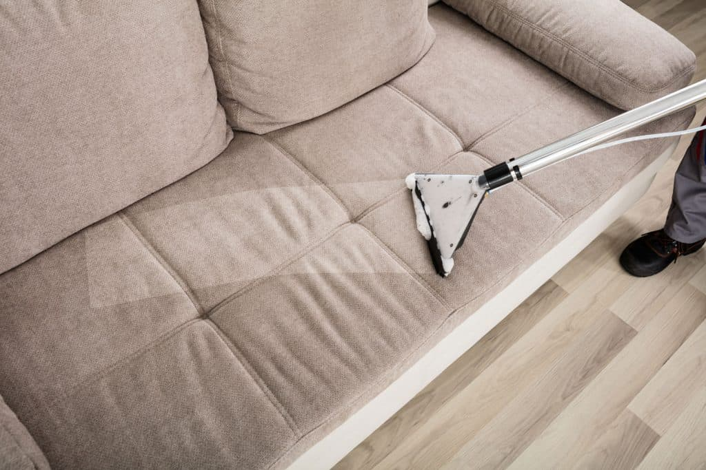 A man using a steam carpet cleaner on the beige couch