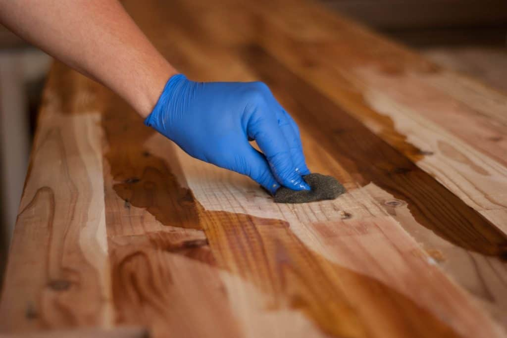 A man wiping the wooden flooring with oil