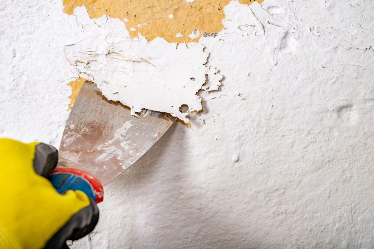 A paint expert removing pain on the wall, How To Remove Paint And Stain From Wood