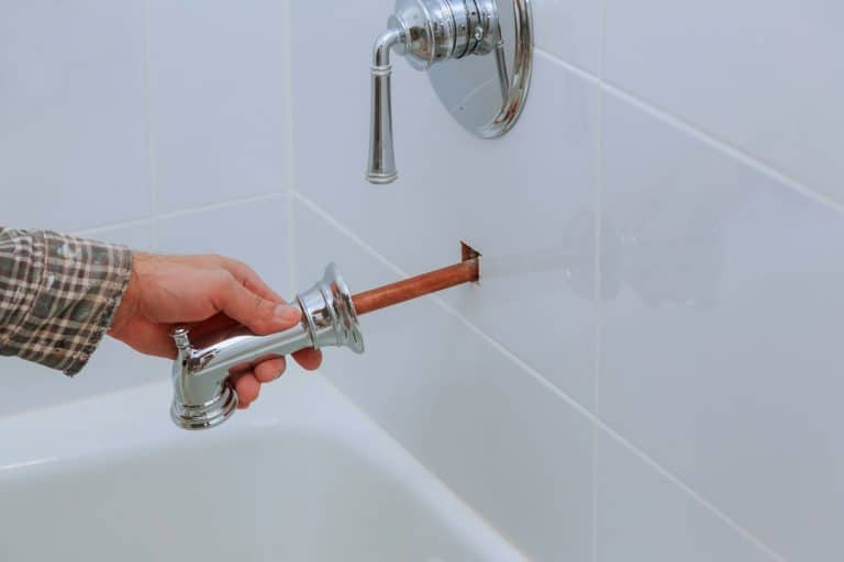 A repair man pulling a faucet pipe out of the bathroom wall, How To Extend A Bathtub Spout Pipe - 2 Methods To Try