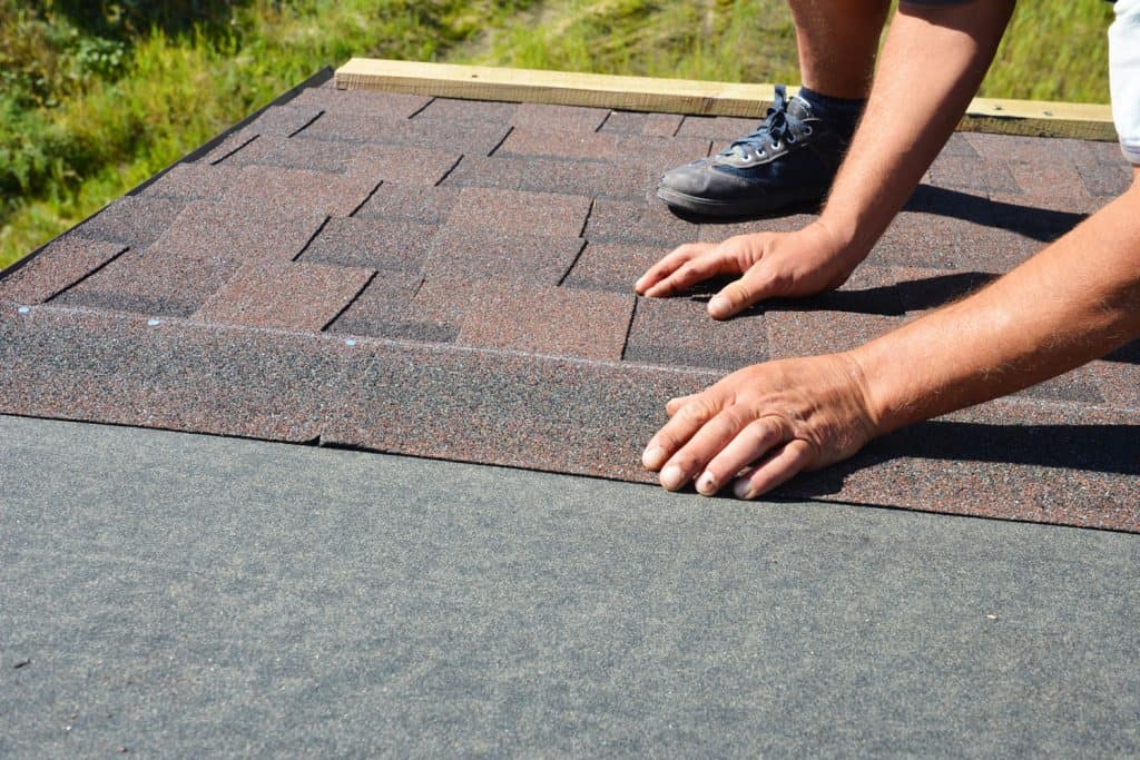 A roof installer putting installing roof shingle underlayment