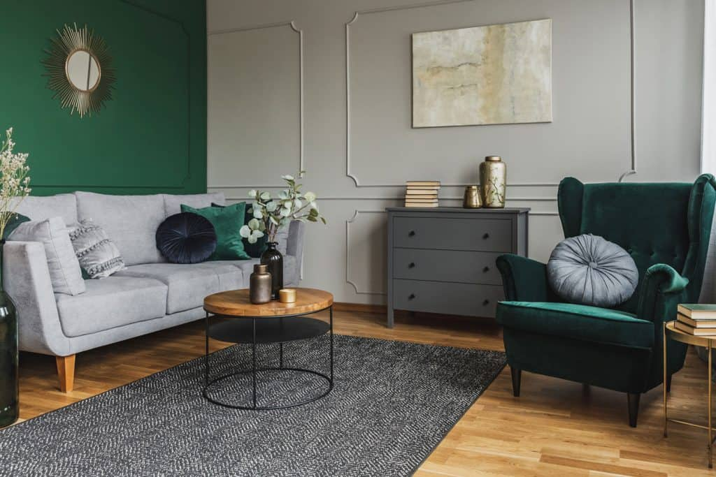 A teal and eclectic themed living room with a green wall and a gray accent chest