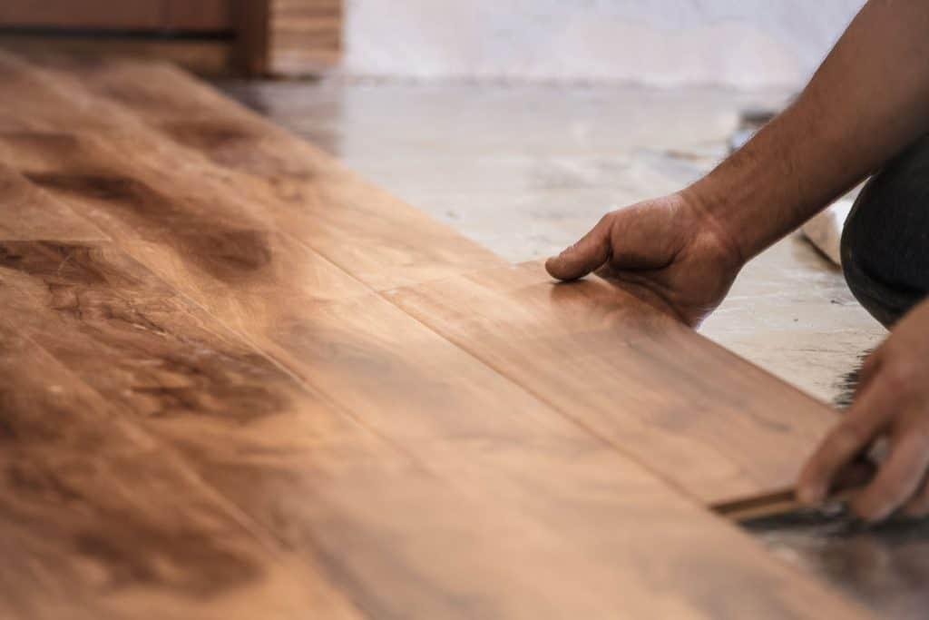 A tile setter inserting wooden flooring